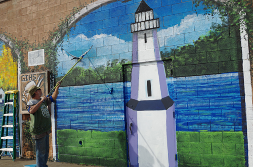 Mural artist Terry Klaaren paints part of the mural that was unveiled Saturday at the Taste of Grand Island Fall Fest. (photo by Larry Austin)
