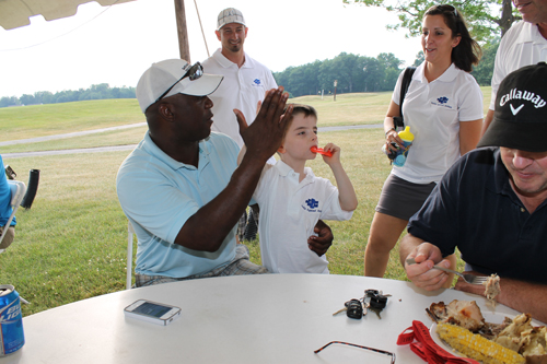Austin Irons high-fives Buffalo Bills legend Thurman Thomas as his father, Matthew Irons, looks on, during the Austin Against Autism fundraiser on Friday, June 29, at River Oaks Golf Club.