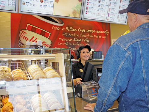 Ashley Gilson, supervisor at Tim Hortons, serves Don Portik on Thursday, the first day of business for the new restaurant at 2366 Grand Island Blvd. (photos by Larry Austin)