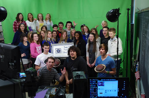 Mark Gorton of Grand Island High School, lower left, talks about the 100th taping of Viking Vision, the school's broadcast news channel. Gorton is surrounded by some of the approximately 50 students who help put the show on the air three times a week. (photo by Larry Austin)