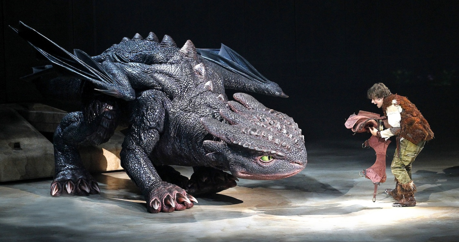 Hiccup (Rarmian Newton) fixes Toothless' tail. (photo by Jeff Busby)