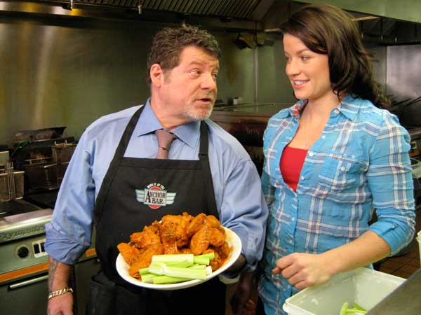 Anchor Bar Executive Chef Ivano Toscani shows `Food Wars` host Camille Ford his famous Buffalo wings. (photo courtesy of the Travel Channel)