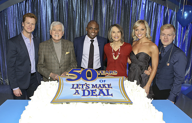 It was a meeting of two casts at the 50th anniversary cake as, from left to right, announcer Jonathan Mangum, legendary host Monty Hall, host Wayne Brady, first-ever model Carol Merrill, model Tiffany Coyne and keyboardist Cat Gray all smile, on a special 50th anniversary episode of `Let's Make A Deal,` Friday, March 1, on the CBS Television Network. (photo by Monty Brinton/CBS ©2013 CBS Broadcasting Inc. All rights reserved.)