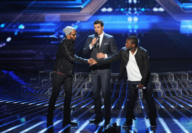 LeRoy Bell (left) shakes hands with Marcus Canty as host Steve Jones speaks on `The X Factor` on FOX. (photo by Ray Mickshaw/FOX)