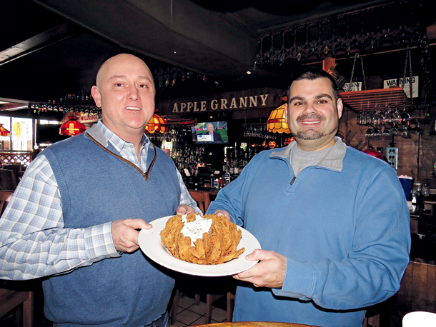 Apple Granny Restaurant owners Michael Burke, left, and Chuck Barber hold up the family eatery's blooming onion. (Photo by Joshua Maloni)