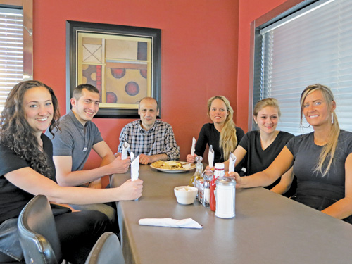 Syros Restaurant owner Bechara Cobti, center, is pictured with his son, Eli, and (clockwise) waitresses Shannon Williams, Sydney Sidoti, Kristy Quarantillo and Elexa Kopty.