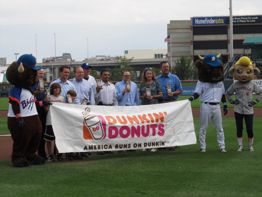 Representatives from Dunkin' Donuts join Buffalo Bisons Manager Tim Teufel to present a total of 312 pounds of coffee to the Food Bank of Western New York at Coca-Cola Field on the team's Fan Appreciation Night. The donation is the result of the `runs for coffee` community initiative, through which Dunkin' Donuts committed to donate one pound of coffee for every run scored at home during the regular season by the Bisons. From left to right: Dunkin' Donuts Field Marketing Manager Eric Stensland; Dunkin' Donuts Operations Manager Patrick Cosentino; Dunkin' Donuts Operations Director Dan O'Neil; Buffalo Bisons Manager Tim Teufel; Dunkin' Donuts Franchisee Raj Patel; a Buffalo Bisons fan; Debbie Billoni; and Food Bank of Western New York Marketing and Public Relations Director Michael Billoni.