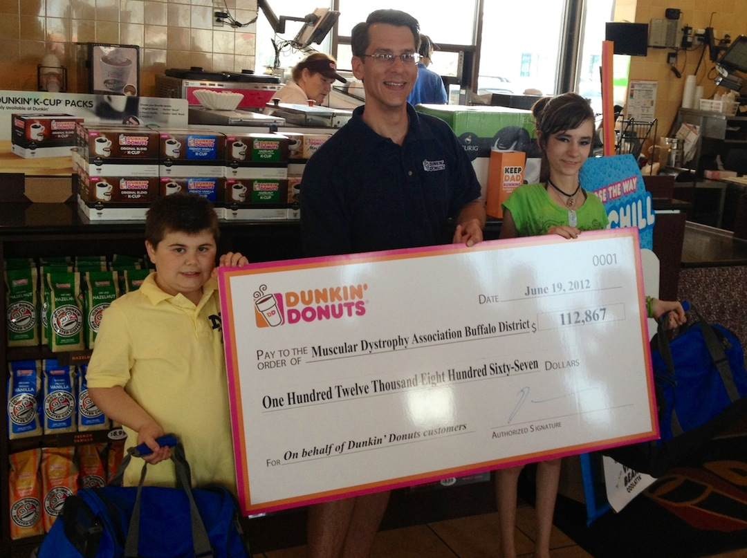 Dunkin' Donuts Franchisee Doug Spolyar (center) presents Muscular Dystrophy Association camp kids Matthew Meranto (left) and Destanee Cope (right) with a check for $112,867 at a send-off for the Buffalo-area campers at the Dunkin' Donuts location in Buffalo.