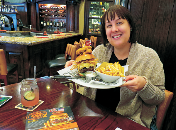 Claire Seveno, sales and marketing manager at Hard Rock Cafe, Niagara Falls, USA, holds an `ATOMIC! Burger,` which is now available as part of the `World Burger Tour.`