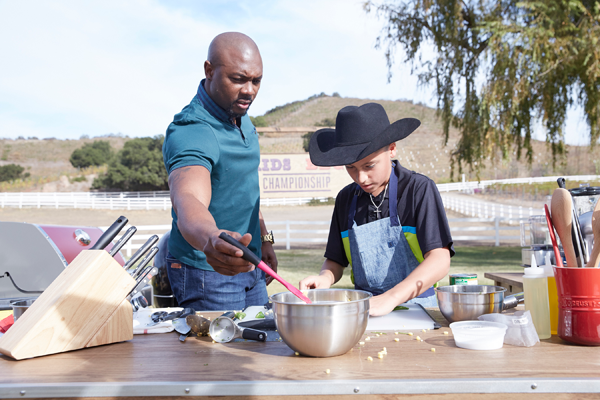 Host Eddie Jackson with competitor Ty Machado on the Food Network's `Kids BBQ Challenge.` (Food Network photo)