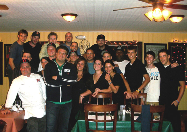 Adam Richman (arms crossed) poses with the Riverstone Grill staff.