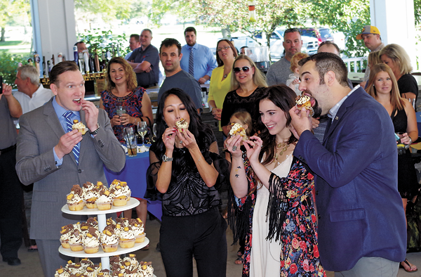 Town Supervisor Nathan McMurray, Kim Pegula of Pegula Sports and Entertainment, and Tara and Jon Bondi of Baked Cupcakery enjoy the One Buffalo Cupcake at a press event unveiling the treat Wednesday. (Photos by Larry Austin)