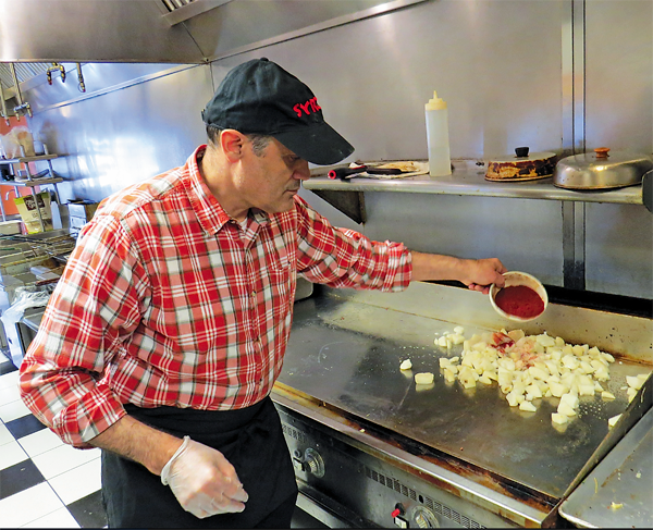 Syros Family Restaurant owner and chef Bechara Cobti works on a pile of home-fried potatoes.