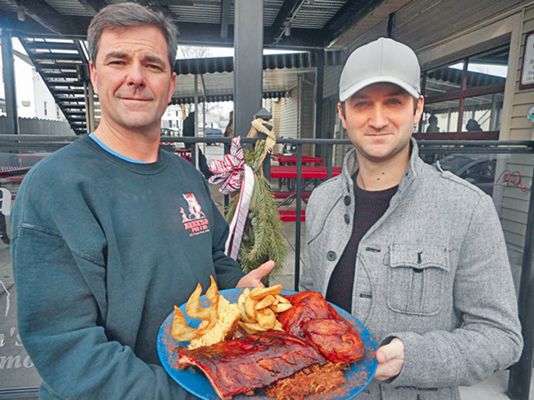 Pictured, from left, Ken Bryan (co-owner of The Brickyard Pub & B.B.Q., Tin Pan Alley, Center Cut and the new Brickyard Brewing Co.) and Corey McGowan hold some of The Brickyard's popular barbecue.