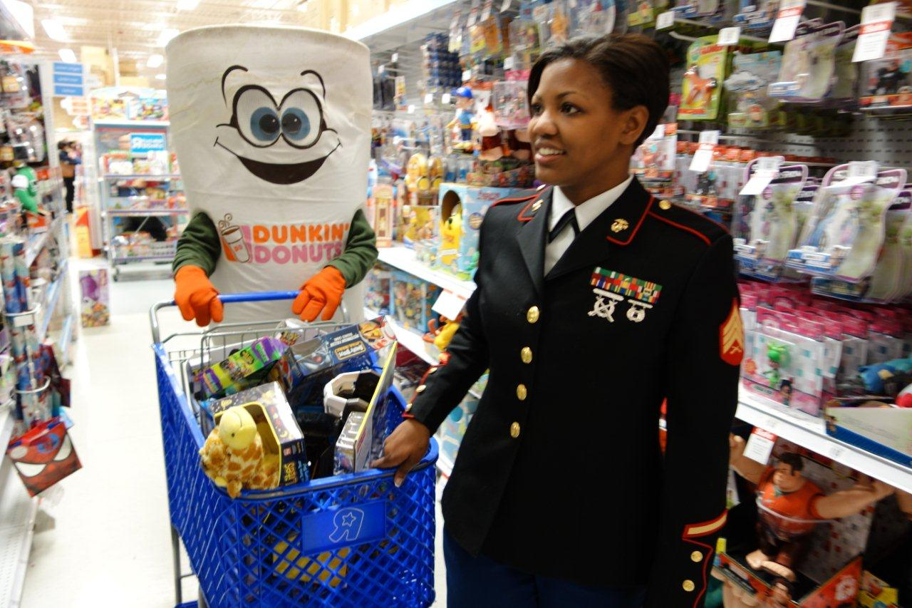 U.S. Marine Corps Reserve Sgt. Keshia L. Toro, coordinator of the Toys for Tots program in Western New York, shops for toys alongside the Dunkin' Donuts Cuppie mascot at the Toys `R` Us in Amherst on Friday, Dec. 14.