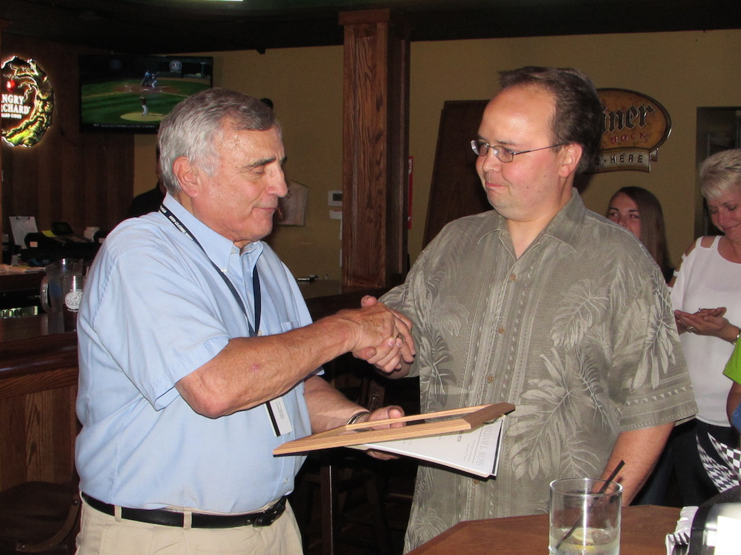Niagara County Legislator Chairman William Ross, left, presents Chris MacKenzie with a plaque signifying the opening of Bailey O'Riley's Village Pub.
