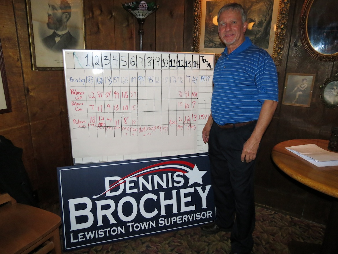 Dennis Brochey stands in front of a white board listing the election totals in each of the Town of Lewiston's 14 districts.