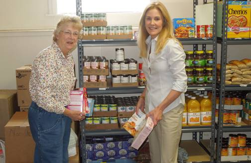 Assemblywoman Jane Corwin, right, and Bonnie Eifert unload donations onto the shelves of the Newfane Baptist Church food pantry.