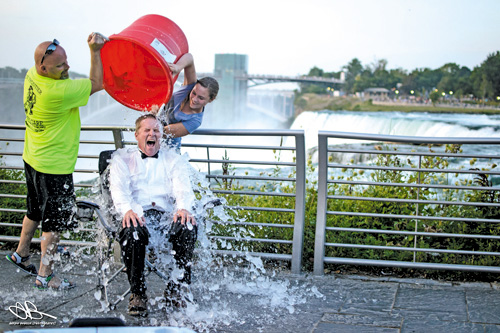 Glenn Bobeck, an Artpark & Company director, completes the `ALS Ice Bucket Challenge` at Niagara Falls State Park, with the assistance of his daughter, Eva, and a volunteer. (photo by Aaron Bobeck)