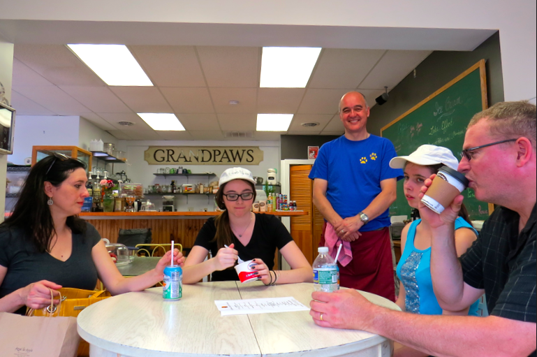 The McGuire family from Williamsville (seated) enjoys Grandpaws Café for Good as owner Andrew Bell looks on. Pictured, from left, are Noreen, Lauren, Brooke and Terry.