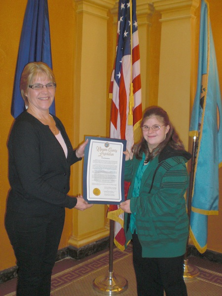 Laura Welder, right, and her mom, Jen, hold up a proclamation in honor of Developmental Disabilities Awareness Month.