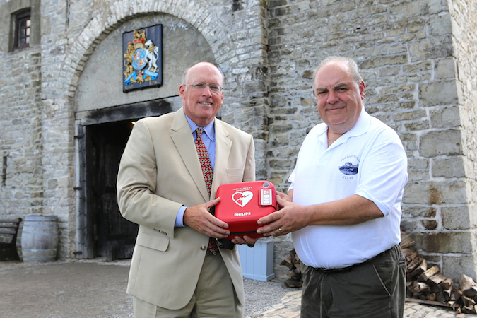 Univera Healthcare President Art Wingerter, left, presents an AED unit to Old Fort Niagara Executive Director Robert Emerson.
