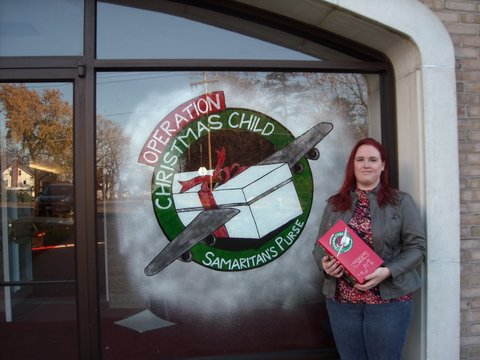 Church member Sandy Wasko stands by the Operation Christmas Child logo she painted.