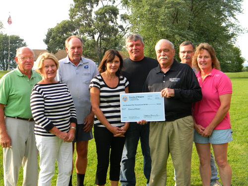 First District Niagara County Legislator Clyde Burmaster visited the Town of Porter this week to present a $150,000 check, funding appropriated earlier by the Niagara River Greenway Commission's Host Communities Standing Committee, for planned improvements at Porter on the Lake Park. Above Burmaster (third from right) joins with Porter on the Lake Committee members in a check presentation Monday afternoon at the park. A similar presentation was made later that day at the Porter Town Board session. (photo by Terry Duffy)