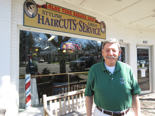 Terry Collesano stands in front of Olde Time Barber Shop on Center Street.