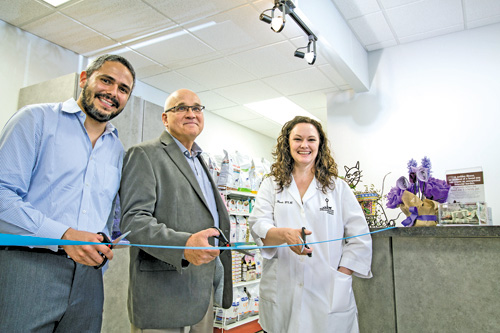 From left: Juan Angel of Onsior, Wayne Usiak of BDA Architecture, and Dr. Kristen Ruest of The Village Vet of Lewiston prepare to cut a ribbon marking her practice's makeover. (photo by Abby-Mae Songin of Barefoot Soul Photography)