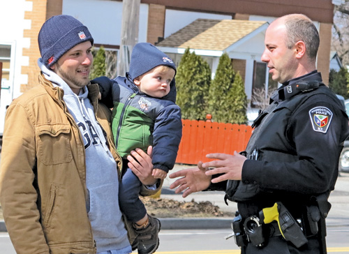 Youngstown Police Officer Greg Quarantillo, on foot patrol on the 500 block of Main Street in the village, is shown talking with resident Kyle Nablo and his son, Dylan. (YPD photo)