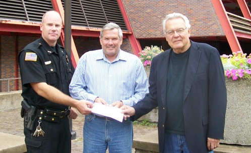 Artpark & Company President George Osborne (right) presented Lewiston Police Department Chief Chris Salada (left) and Town of Lewiston Supervisor Steve Reiter with a check for $3,600 on Wednesday. The municipality saved the organization time and money this past summer by setting up the Robert Moses Parkway slip ramp barricades. (photo by Joshua Maloni)