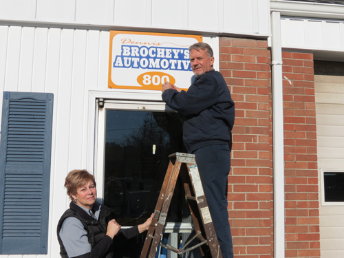 Dennis Brochey takes down the sign outside of his Center Street auto shop as his wife, Cathy, holds the ladder.