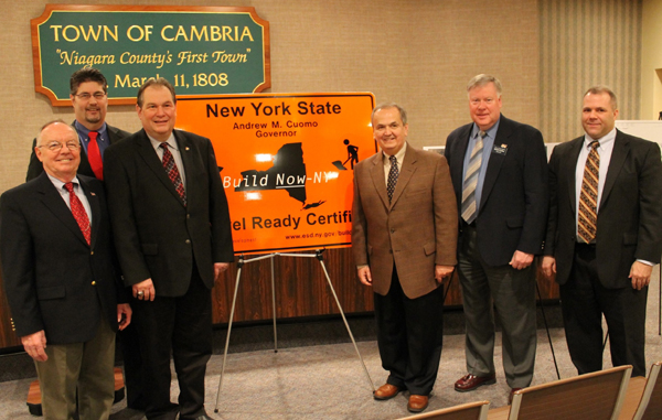 Local leaders celebrate the designation of the new 152-acre Cambria Technology Park as a `Shovel-Ready Certified` site at a Thursday morning press conference. Flanking an orange highway sign provided by Empire State Development Corp. that designates the site as shovel-ready are Supervisor Wright Ellis (left), National Grid Regional Executive Dennis Elsenbeck, Assemblyman John D. Ceretto, Sen. George D. Maziarz, Niagara County Legislator Dave Godfrey and Legislature Economic Development Committee Chairman Rick Updegrove. The shovel-ready certification means that the site can be developed without lengthy permitting processes. National Grid provided a $300,000 grant to the Niagara County Center for Economic Development in 2010 that helped make the site `shovel-ready.`