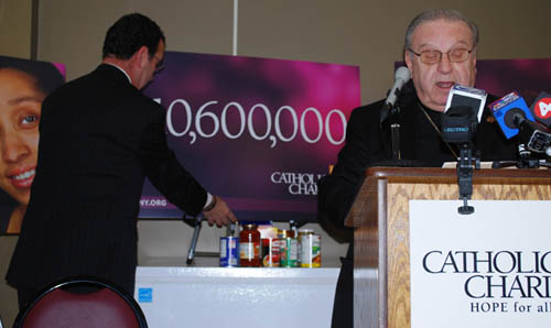 Bishop Kmiec announces theme and goal for 2012 Catholic Charities Appeal as Chairman David Nasca works in the background.