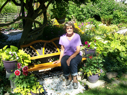 Dotty Gara sits in her garden, outside of her Lewiston home.