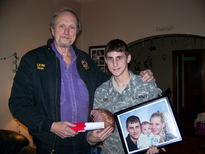 Lion Ron Craft presents Christmas gifts to a service member.