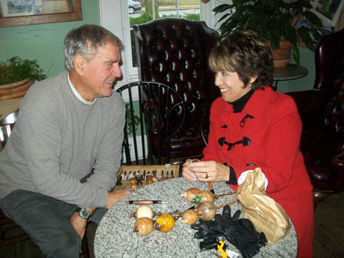 Woodworker Lloyd Draper shows his Christmas ornaments to Carol Calato.