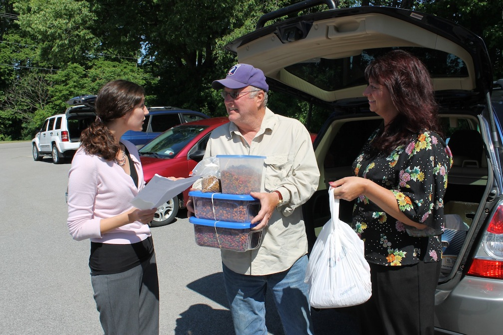 As Grace Wingard (right) of the Donner Creek Veterinary Clinic looks on, Niagara County Office for the Aging Home-Delivered Meals Coordinator Sarah Lilley goes over a checklist with volunteer James Muscoreil, who is loading up tubs of dog and cat food for animal companions living with area seniors.