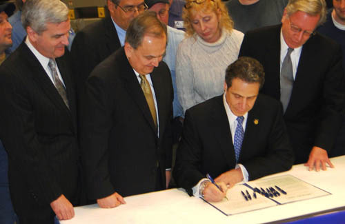 With Assemblyman Jim Hayes, R-Amherst, Sen. George D. Maziarz, R-Newfane, and Assemblyman Robin Schimminger, D-Kenmore, all looking on, Gov. Andrew M. Cuomo signs the Maziarz-authored `Recharge New York` program into law.  Recharge New York is a major power-for-jobs program that makes previous short-term power-for-jobs programs permanent, offering low-cost power to businesses looking to expand or locate their operations in New York state.