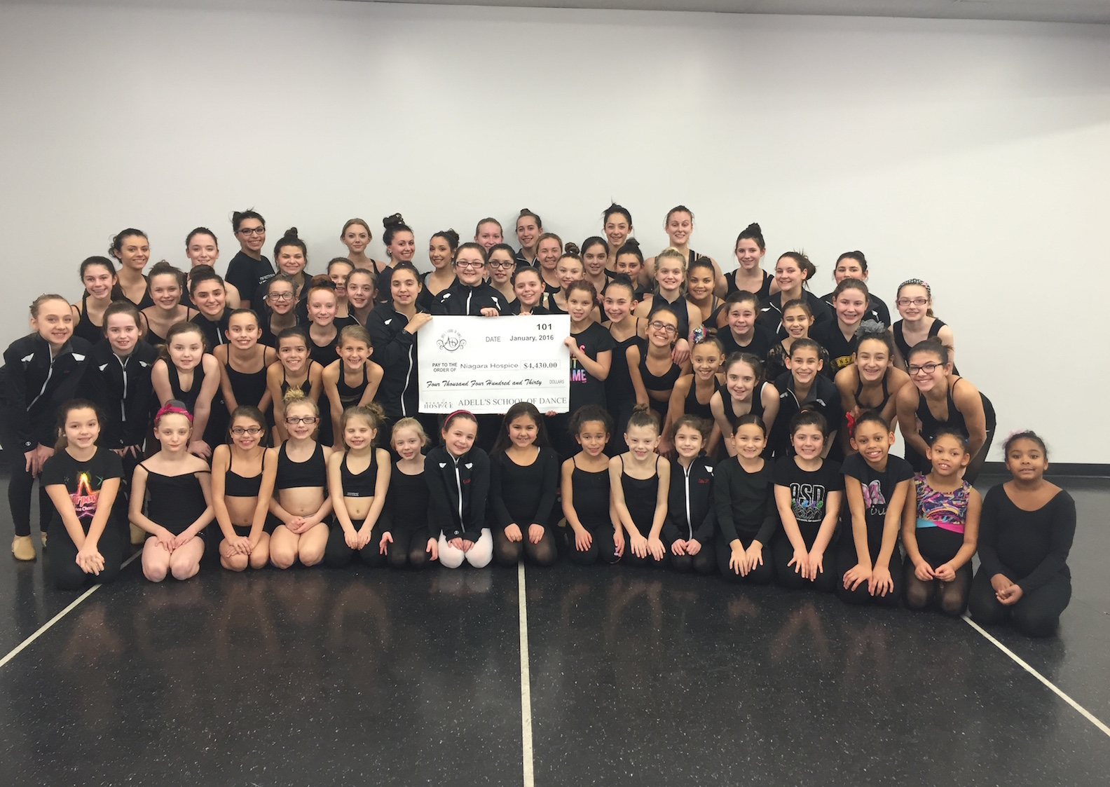 Adell's School of Dance performance/competition team members hold a check for $4,430, presented to Niagara Hospice as a result of their Mighty Niagara Discount Card Fundraiser.