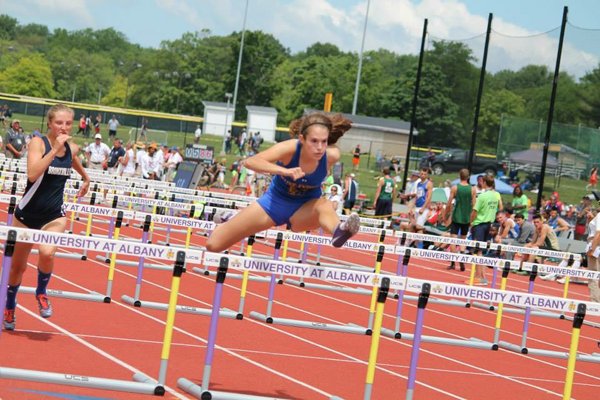 Alex Laubret, in her fifth track meet of the season, jumps over a hurdle and heads toward the finish line, striving to reach (hopefully) another victory.