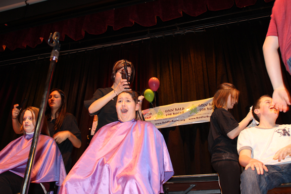 Maria Malvestuto gets ready to cut Destyne Kohn's hair, Orleans/Niagara BOCES teacher Lori Smith shaves Caelee Faultersack's hair and Melyssa Myers gets ready to shave Cameron Miller's hair.