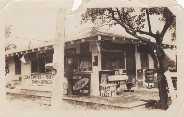 This picture was taken in the early 1920s, when the stand first opened. Products sold were advertised on signs and customers ordered at the windows. Edwin DeVantier is standing inside the front window as he waits on a customer.