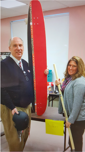 Principal/President Ron Buggs with Tracy Beebe and auction items.
