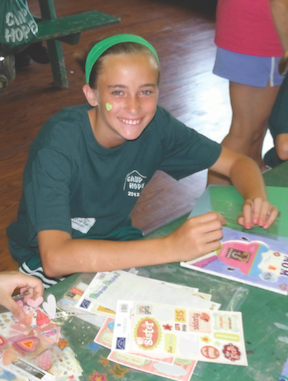 Camper Danielle enjoys using her artistic talent to make her memorial picture frame at Camp Hope last summer.