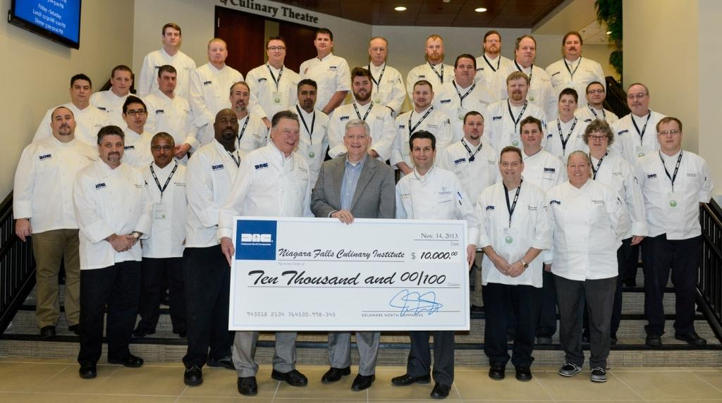 Delaware North Vice President of Shared Services Kevin Kelly (first row, center) and Delaware North chefs present the scholarship check to NCCC's chef Mark Mistriner (first row, right).