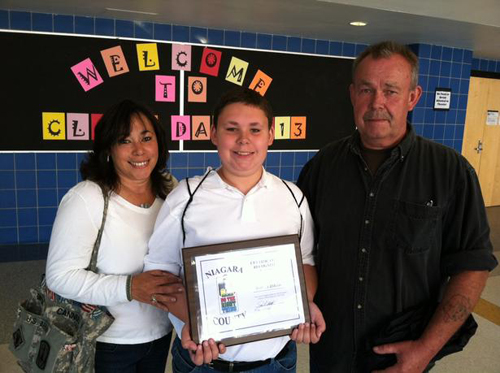 Robert Dikcis shows off his Do The Right Thing plaque with his parents Robert and Gigi Dikcis.