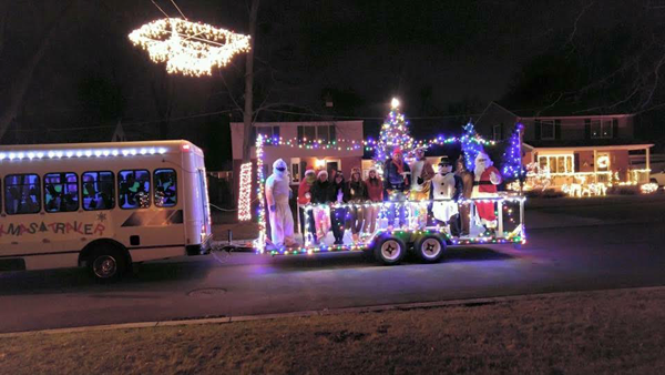 A 25-foot trailer decorated with lights and carolers helps spread Christmas cheer around North Tonawanda, while collecting donations for the North Tonawanda Food Pantry. (Photo by Martha Russell)