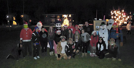 The carolers pose for a pictures with the North Tonawanda High School mascot (Lumberjack) during the tree-lighting ceremony last year. (Photo courtesy of XMAS Trailer's Facebook page)